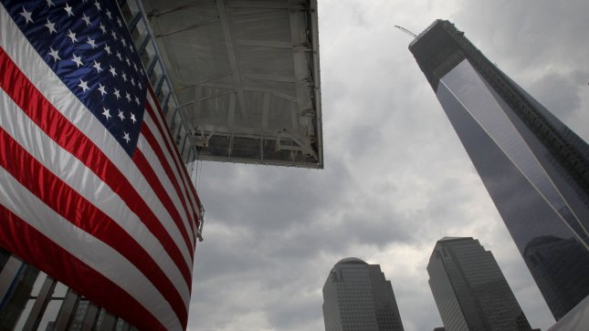 One world Trade center stands to the right of a flag that hangs on 4 World Trade Center. UPI/John Angelillo