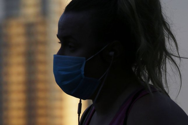 Even around a coughing super spreader in a small room, researchers say masks can prevent the spread of coronavirus. Pictured, a women wears a protective face mask in New York City in April. Photo by John Angelillo/UPI