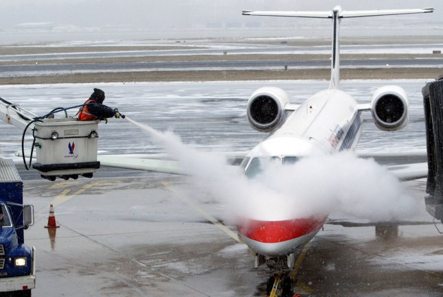 A worker sprays an American Eagle Regional Jet with de-icer as it prepares to take off during a light snowfall at Ronald Reagan National Airport in Alexandria , VA on January 22, 2005. (UPI Photo/Bill Greenblatt)