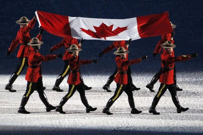 Members of the Royal Canadian Mounted Police with the Canadian flag (File/UPI/Brian Kersey)