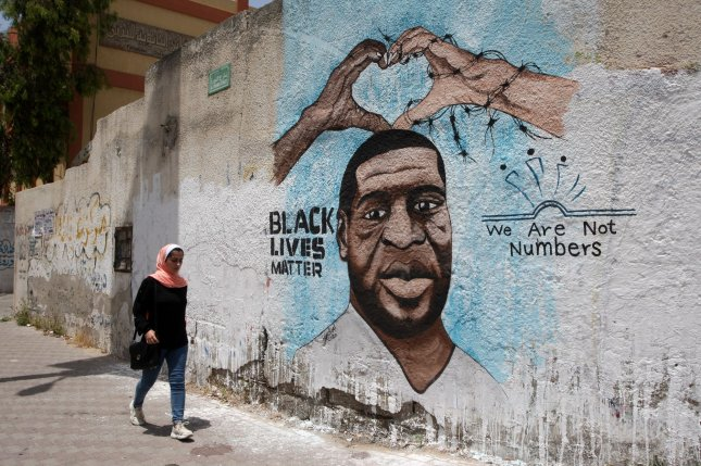 A Palestinian woman walks June 21, 2020, next to a Gaza City mural depicting George Floyd, an unarmed Black man who died while in Minneapolis police custody on May 25, 2020. File Photo by Ismael Mohamad/UPI