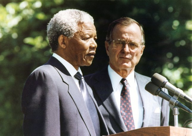 Nelson Mandela (L), who was released from prison after 27 years Feb. 11, 1990, speaks at the White House alongside U.S. President George H.W. Bush 4 1/2 monhs later, on June 25, 1990. File Photo/UPI