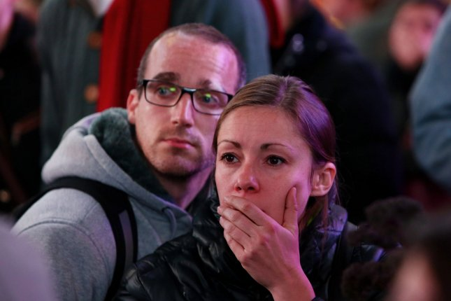 People react as numbers are broadcast on a giant video screen showing Republican candidate Donald J. Trump pulling ahead as crowds gather in Times Square on Election Day. Clinton has taken the popular vote lead, but lost the Electoral College. Photo by Monika Graff/UPI