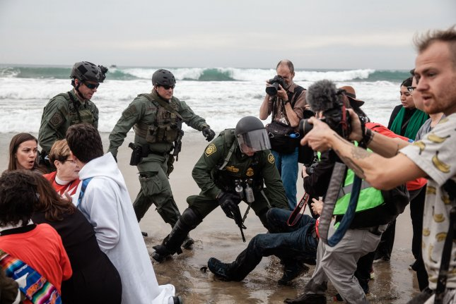 Border patrol agents scuffle with demonstrators at Border Field State Park near San Diego, Calif., on Monday. Photo by Ariana Drehsler/UPI