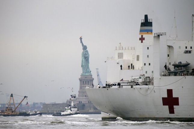 The USNS Comfort Navy ship moves past the Statue of Liberty on route to dock in the Hudson River in New York City on Monday to serve as a floating hospital. Photo by John Angelillo/UPI