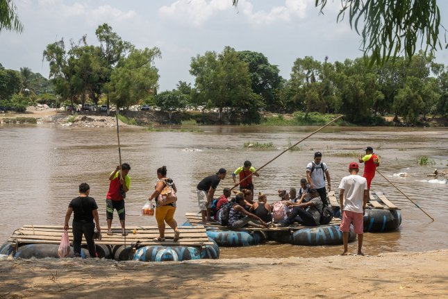 Migrants ride an inflatable raft on the Suchiate River from Tecun Uman, Guatemala while a smuggler waits for their arrival in Ciudad Hidalgoon, Mexico on May 9. File Photo by Ariana Drehsler/UPI