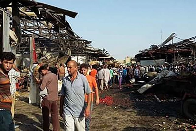 People gather at the scene of a truck bomb attack in Jameela market in the predominantly Shiite neighborhood of Sadr City, Baghdad, Iraq, Aug. 13, 2015. The massive truck bomb ripped through the popular Baghdad food market in the Iraqi capital's crowded neighborhood in the early morning hours on Thursday, killing tens of people, in one of the deadliest single blasts in the capital in years, police officials said. photo by Hadeer Abbass /UPI