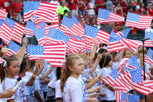 Children wave American flags after singing God Bless America, before the Atlanta Braves-St. Louis Cardinals baseball game at Busch Stadium in St. Louis on August 24, 2013. UPI/Bill Greenblatt