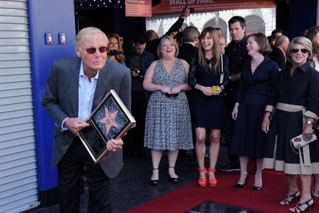 Actor Adam West holds a replica plaque and gets playful with photographers to the delight of family members, during an unveiling ceremony honoring him with the 2,468th star in Los Angeles on April 5, 2012. File Photo by Jim Ruymen/UPI