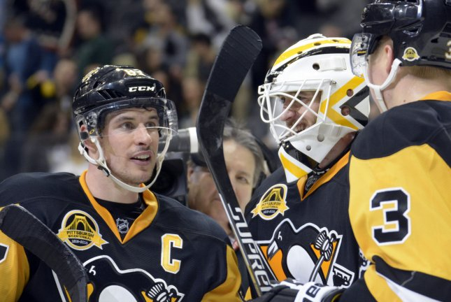 Pittsburgh Penguins center Sidney Crosby (87) joins Pittsburgh Penguins goalie Matt Murray (30) and Pittsburgh Penguins defenseman Olli Maatta (3) in celebrating the Penguins 4-2 win against the Carolina Hurricanes at the Consol Energy Center in Pittsburgh on March 17, 2016. Photo by Archie Carpenter/UPI