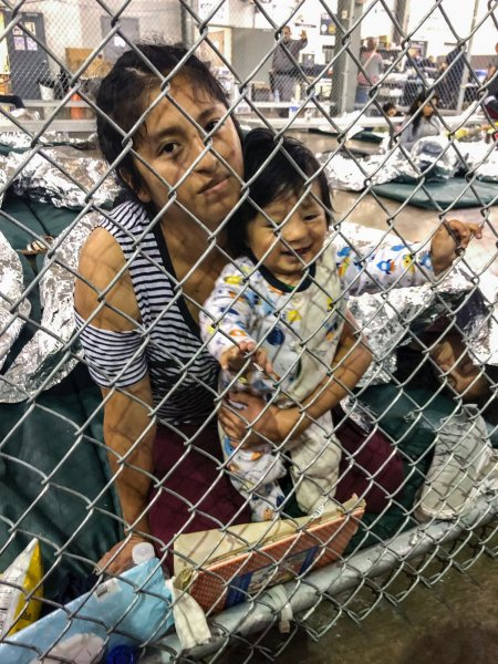 A migrant woman holds her child behind cyclone fencing at the Central Processing Center in McAllen, Texas, on July 13, 2019. File Photo by Office Congresswoman of Doris Matsui/UPI