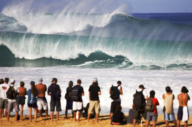 Spectators watch massive waves crash at the venue for the Rip Curl Pro Pipeline Masters at the Banzai pipeline on the North Shore of Oahu, Hawaii on December 13, 2004.. The contest was placed on hold due to stormy surf conditions which rocked the North Shore. The Rip Curl Pipeline Masters is the final event for the men on the 2004 Fosters ASP World Championship Tour and features the top 45 surfers and three wild card entrants. (UPI Photo/Pierre Tostee/ASP Tostee).