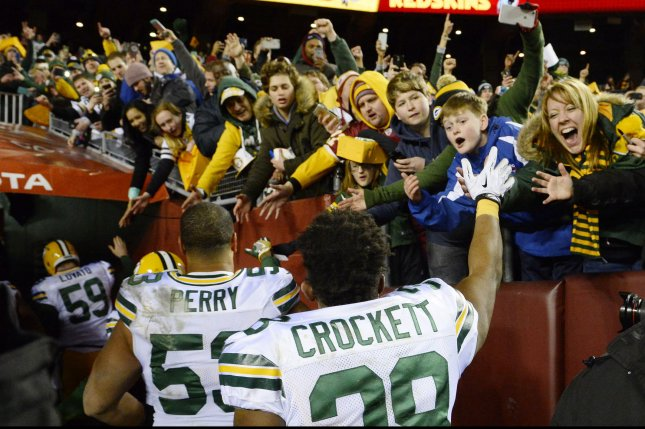 Green Bay Packers' John Crockett (38) and Nick Perry (53) are congratulated by fans after defeating the Washington Redskins 35-18 in their NFC Wild Card game at FedEx Field in Landover, Maryland, January 10, 2016. Photo by David Tulis/UPI