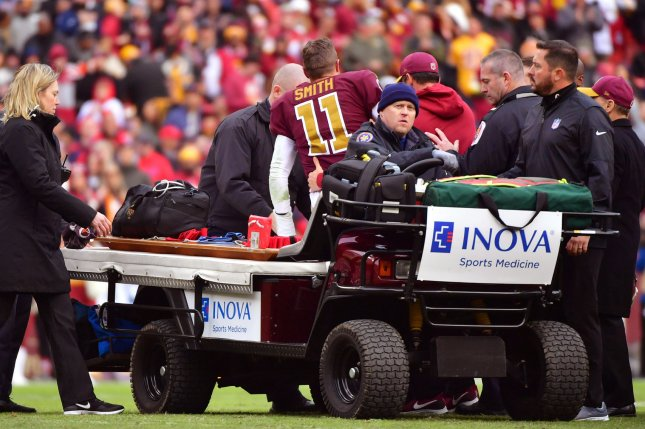 Washington Redskins quarterback Alex Smith (11) is helped off the field after being injured in the third quarter against the Houston Texans on November 18 at FedEx Field in Landover, Md. Photo by Kevin Dietsch/UPI