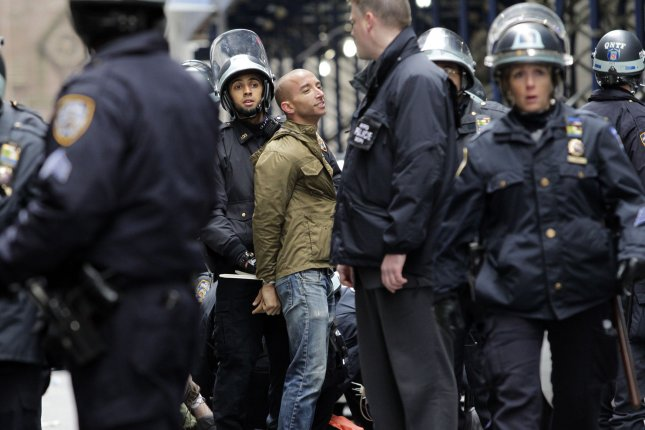 NYPD officers stand around an Occupy Wall Street protester with his hands tied behind his back near the New York Stock Exchange on Wall Street In New York City on November 17, 2011. (John Angelillo/UPI)