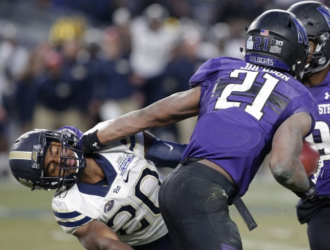 Northwestern Wildcats running back Justin Jackson stiff arms Pittsburgh Panthers Dennis Briggs at the Pinstripe Bowl at Yankee Stadium in New York City on December 28, 2016. Northwestern running back Justin Jackson had a record-setting performance against Pitt with 224 rushing yards against the Panthers to set a Pinstripe Bowl record and his three touchdowns lead the Wildcats past the Panthers in a 31-24 victory. Photo by John Angelillo/UPI