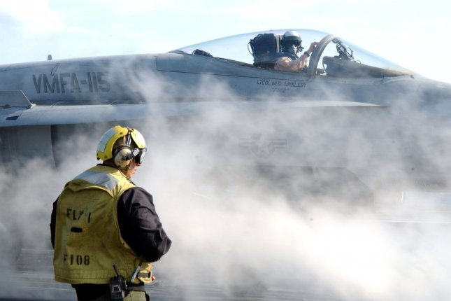An Aviation Boatswain's Mate directs an F/A-18 Hornet into position to be launched from the flight deck aboard the aircraft carrier USS Harry S. Truman on March 20, 2003. On March 20, 2003, U.S.-led coalition forces begin military operations in Iraq. File Photo by Michael W. Pendergrass/U.S. Navy