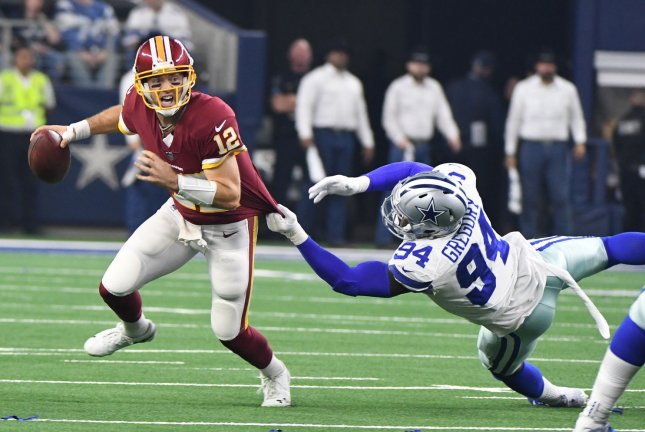 Washington Redskins quarterback Colt McCoy (12) scrambles away from Dallas Cowboys defensive lineman Randy Gregory during their game on Thursday at AT&T Stadium in Arlington, Texas. Photo by Ian Halperin/UPI