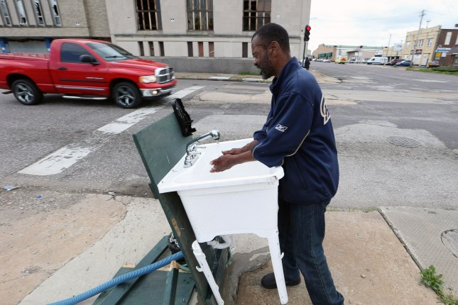 Jonathan Pasley turns on the water to wash his hands with cold water and no soap at a station hooked up to a fire hydrant for those on the street during the COVID-19 pandemic. File Photo by Bill Greenblatt/UPI