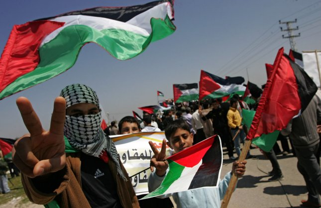 Demonstrators hold Palestinian flags during a rally marking Land Day in Beit Lahiya, northern Gaza, March 30, 2011. as hundreds of people across Israel and Palestinian territories were holding a series of rallies marking Land Day, recalling an incident in 1976 when Israeli troops shot and killed six people during protests against land confiscations. UPI/Ismael Mohamad.