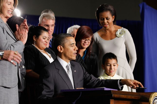 U.S. President Barack Obama signs the Healthy, Hunger-Free Kids Act of 2010 with first lady Michelle Obama (R), 3rd-grader Luis Avilar-Rurcios (2nd R) and 7th-grader Tammy Nguyen (3rd R) at Harriet Tubman Elementary School December 13, 2010 in Washington, DC. In an effort to provide children with better school lunches and breakfasts, the new law puts $4.5 million in the hands of child nutrition programs, sets nutrition standards on school vending machines, helps create school gardens and makes sure that quality drinking water is available during meal times. UPI/Chip Somodevilla/POOL