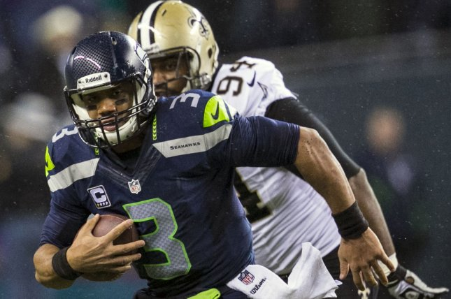 Seattle Seahawks quarterback Russell Wilson (3) scrambles away from New Orleans Saints defensive end Cameron Jordan(94) during the third quarter at CenturyLink Field in Seattle, Washington on December 2, 2013. Wilson completed 22 of 30 passes for 310 yards and three touchdowns and rushed for 47 yards in the Seahawks 34-7 win over the Saints to take the best record team in the NFL (File/UPI/Jim Bryant)