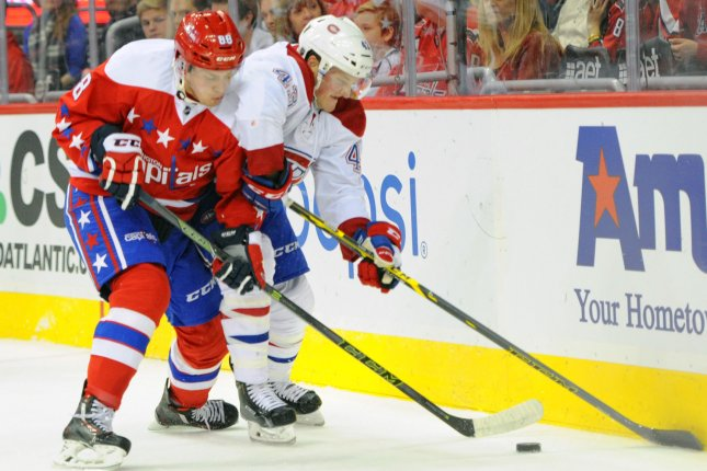 Washington Capitals defenseman Nate Schmidt (88) battles for a loose puck against the boards with Montreal Canadiens left wing Daniel Carr (43) in the first period at the Verizon Center in Washington, D.C. on December 26, 2015. Photo by Mark Goldman/UPI
