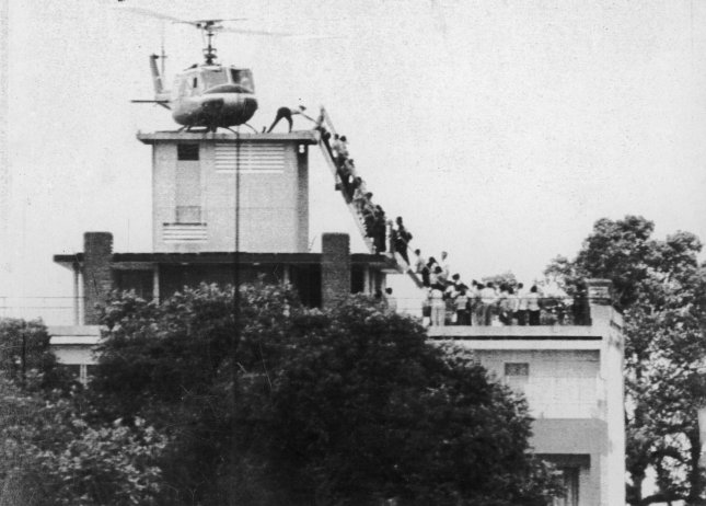 A crew member from an Air America helicopter helps evacuees up a ladder on the roof of 18 Gia Long Street in Saigon on April 29, 1975, shortly before the city fell to advancing North Vietnamese troops. File Photo by Hugh Van Es/UPI