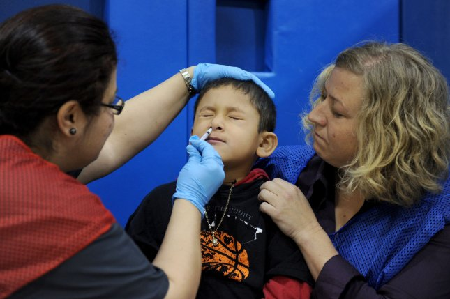 A young boy receives an inhaled H1N1 flu vaccine dose from a nurse at Carlin Springs Elementary School in Arlington, Va., on January 7, 2010. On October 24, 2009, U.S. President Barack Obama declared a national emergency related to the outbreak of the H1N1 flu virus, also known as swine flu. File Photo by Roger L. Wollenberg/UPI