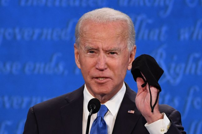 Joe Biden holds up his face mask during the final presidential debate on October 22, 2020. The president-elect detailed a five-point COVID-19 vaccine plan Friday. Photo by Kevin Dietsch/UPI .