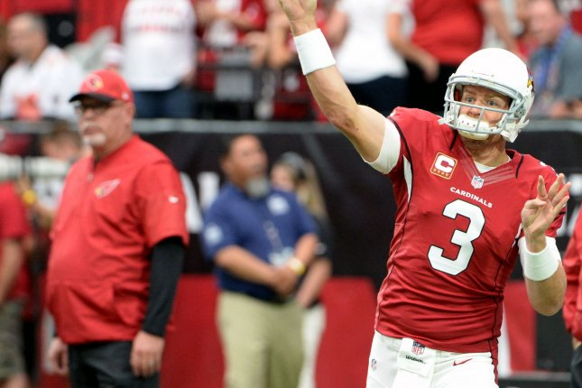 Arizona Cardinals quarterback Carson Palmer throws a pass as he warms up for the Cardinals-Tampa Bay Buccaneers game at University of Phoenix Stadium in Glendale, Arizona, September 18, 2016. Looking on at the left is Cardinals head coach Bruce Arians. Photo by Art Foxall/UPI
