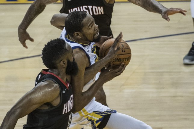 5590de77b2d Golden State Warriors forward Kevin Durant (C) drives by Houston Rockets  guard James Harden (L) in Game 1 of the Western Conference semifinals  Sunday at ...