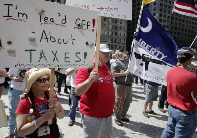 Janice (L) and Charlie Bricker hold signs at a tea party rally at Daley Plaza in Chicago on April 15, 2010. The rally was one of thousands held by tea party activists around the country on tax day. UPI/Brian Kersey