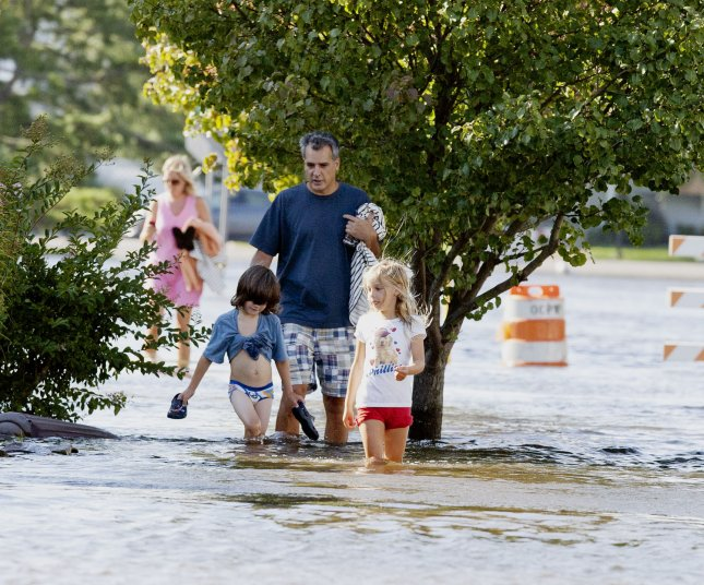 A family in Ocean City , New Jersey wade through water a they walk from their home after Hurricane Irene left many flooded streets August 28, 2011. The Category 1storm did not damage the Jersey Shore as much as expected, however massive flooding is expected. UPI/John Anderson