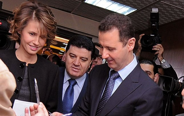 A handout picture released by the Syrian Arab News Agency (SANA) shows Syrian president Bashar al-Assad accompanied by his wife Asma (L), posing for a photograph while casting his vote, during the referendum on a new constitution, at a polling station, in Damascus, Syria, on February 26, 2012. Syrians began voting February 26 on a new constitution that the government says will introduce political pluralism. More than 14,000 polling stations opened nationwide for about 15 million eligible voters. The opposition announced a boycott of the referendum. UPI.