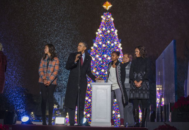 US President Barack Obama (C-L) lights the National Christmas tree with his daughters Malia (L) and Sasha (C), his mother-in-law Marian Robinson (C-R) and wife Michelle Obama (R) during the 91st National Christmas Tree Lighting Ceremony on the Ellipse south of the White House in Washington, DC, on December 6, 2013. The lighting of the tree is an annual tradition attended by the US President and the First Family. President Calvin Coolidge lit the first National Christmas tree, a 48-foot Balsam fir, in 1923. UPI/Jim Lo Scalzo/Pool
