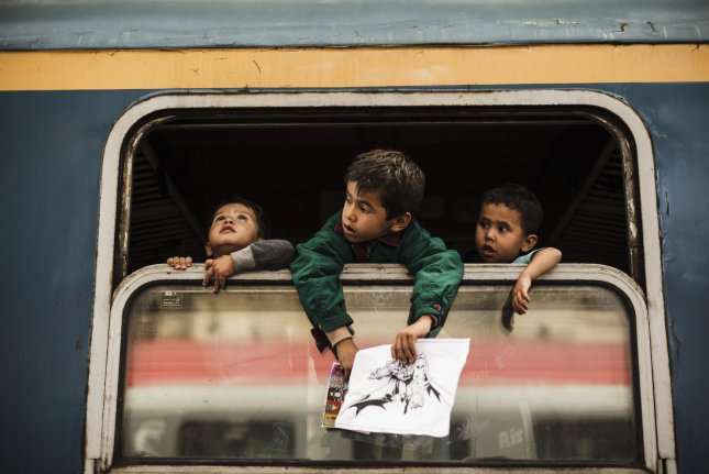Afghan children looks out a window of a commercial train heading towards Vienna in the Keleti train station in Budapest, Hungary on September 6, 2015. Photo by Achilleas Zavallis/UPI