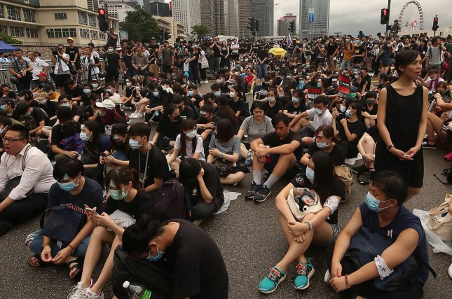Protesters block a road as they gather outside barriers lined with Hong Kong police guarding the Legislative Government headquarters in Hong Kong on Monday. Photo by Stephen Shaver/UPI