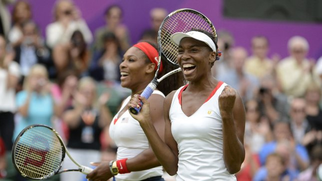 Venus (R) and Serena Williams after winning the gold medal. UPI/Brian Kersey