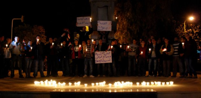 Anti-government protesters hold the Syrian flags and candles at Shuhada or (Martyrs) Square in Swaeda in the southern part of Syria on March 28, 2011. The demonstration was for the victims who were apparently killed by the security forces in Daraa and other cities along in the country. UPI/Ali Bitar