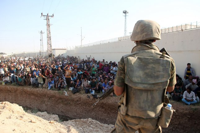 Turkey has been attacked on its border with Syria by both the Islamic State and by the Kurdish Workers Party militant group, also known as the PKK. Pictured: Turkish soldiers guard while hundreds of Syrian refugees wait at the Syrian side of the border crossing in Akcakale, Sanliurfa province, south-eastern Turkey, June 14 2015. They are trying to cross to the Turkish side as they are fleeing from the fighting between the Kurdish People's Protection Units (YPG) military group and Islamic State (ISIS). File Photo by Ebrahem Khadir/ UPI
