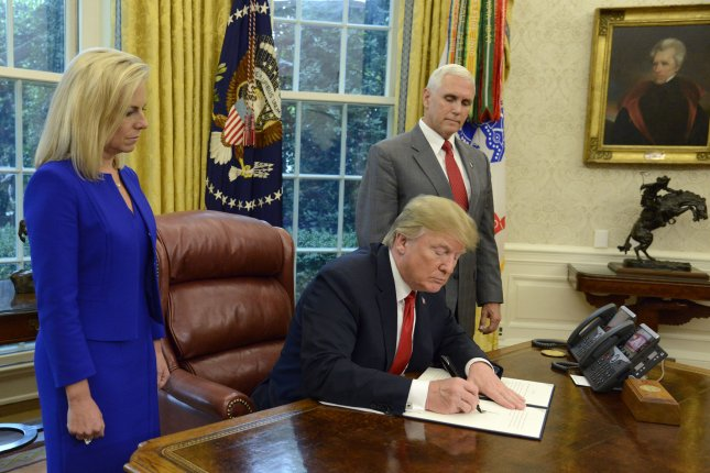 President Donald Trump signs an executive order stopping the separation of immigration families, as DHS Secretary Kirstjen Nielsen (L) and Vice President Mike Pence look on in the Oval Office of the White House on Wednesday. Photo by Mike Theiler/UPI