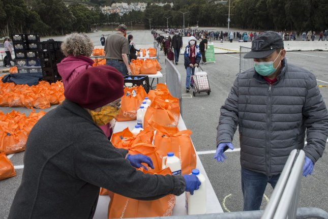 People receive bags of food from the San Francisco-Marin Food Bank in the parking lot of the Cow Palace in Daly City, Calif., on Friday. The Trump administration announced plans to spend $3 billion to purchase food from farmers and ranchers to then funnel to the nation's food banks. Photo by Terry Schmitt/UPI
