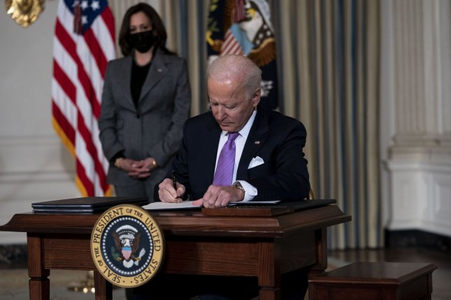 President Joe Biden, joined by Vice President Kamala Harris, signs a series of executive actions to promote racial equality in the State Dining Room of the White House on Tuesday. Pool Photo by Doug Mills/UPI
