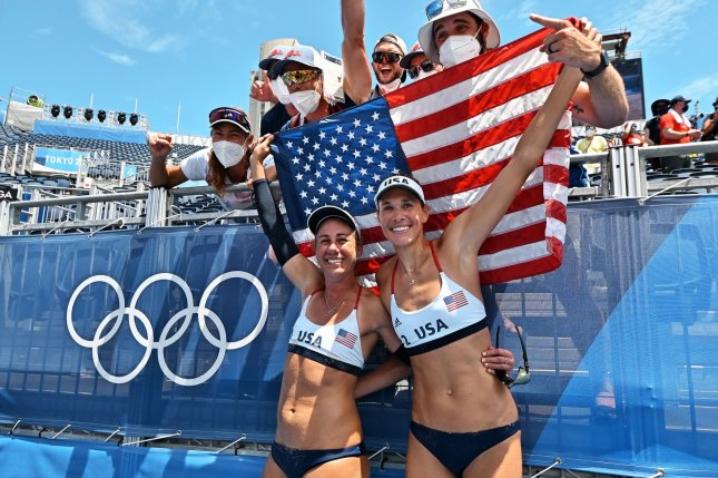 Gold medalists April Ross (L) and Alix Klineman of the United States celebrate their victory on Friday during the Tokyo Olympics women's beach volleyball medal ceremony at Shiokaze Park in Tokyo, Japan. Photo by Keizo Mori/UPI