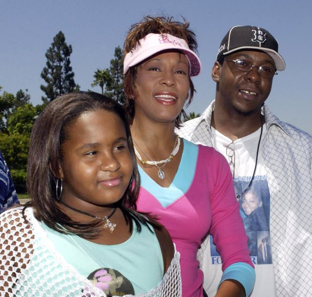 Whitney Houston (C) poses with her husband, Bobby Brown and their daughter Bobbi Kristina (L) at Disneyland in Anaheim, California on August 7, 2004. Houston has filed for divorce from Brown, her spokeswoman said on Wednesday, September 13, 2006 following 14 tumultuous years of marriage and tabloid headlines. (UPI Photo/Jim Ruymen/file photo)