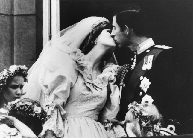 In the year's big happy story, the Prince and Princess of Wales kiss on the balcony of Buckingham Palace after their wedding at St. Paul's Cathedral on July 27, 1981. The heir to the British throne, Prince Charles, married the Lady Diana Spencer to the delight of millions. UPI File Photo