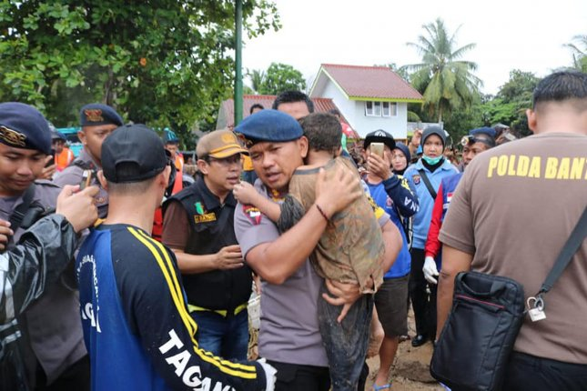 A police officer carries an injured boy, rescued from the remains of a collapsed hotel, following a tsunami in Banten province, Indonesia, Sunday. Photo by Banten Police/UPI
