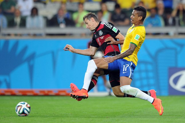Luis Gustavo of Brazil competes with Miroslav Klose (L) of Germany during the 2014 FIFA World Cup Semi Final match at the Estadio Mineirao in Belo Horizonte, Brazil on July 08, 2014. (UPI/Chris Brunskill)
