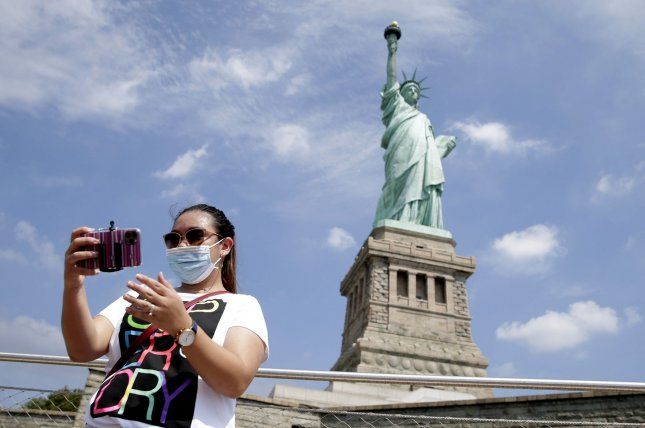 A sightseer wears a face mask next to The Statue of Liberty. Mask-wearing may help reduce face-touching, a new study finds. Photo by John Angelillo/UPI